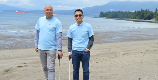Two men in DP World branded light blue shirts picking up trash from the beach shoreline